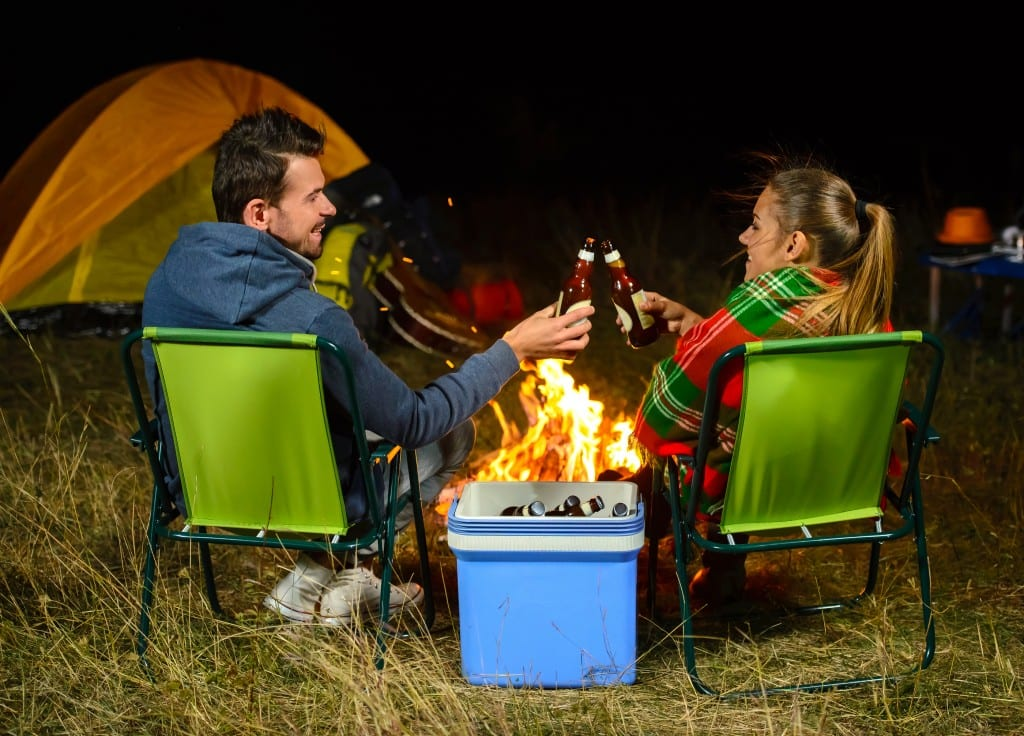 Romantic evening. Couple campfire while camping drinking beer