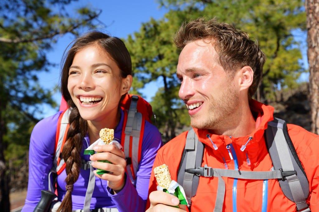 Couple eating muesli bars hiking